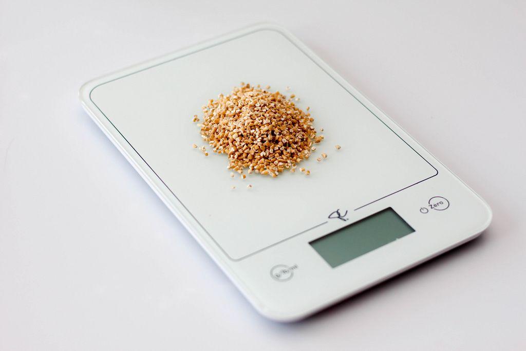 Küchenwaage mit Quinoa vor weißem Hintergrund