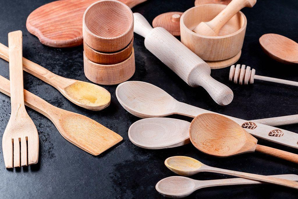 Küchenzubehör und Kochutensilien mit Holzlöffel auf schwarzem Hintergrund