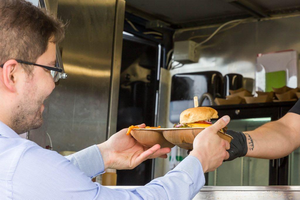 Kunde nimmt seinen veganen Cheeseburger entgegen