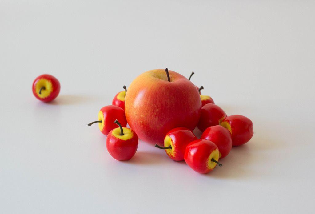 Künstliche Äpfel und ein echter Apfel auf weißem Tisch