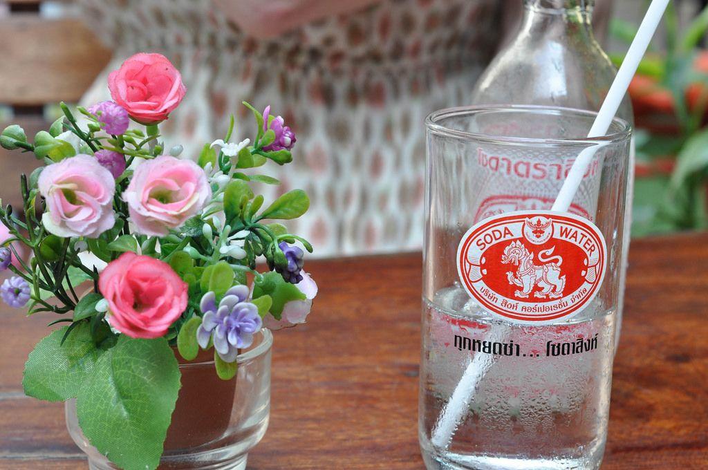 Künstliche Blumen und ein Glas Sodawasser mit Strohhalm