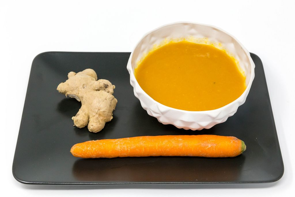 Kürbis-Kokosnuss-Cremesuppe mit Inger auf einem schwarzen Teller mit einer Ingwerwurzel und einer Möhre