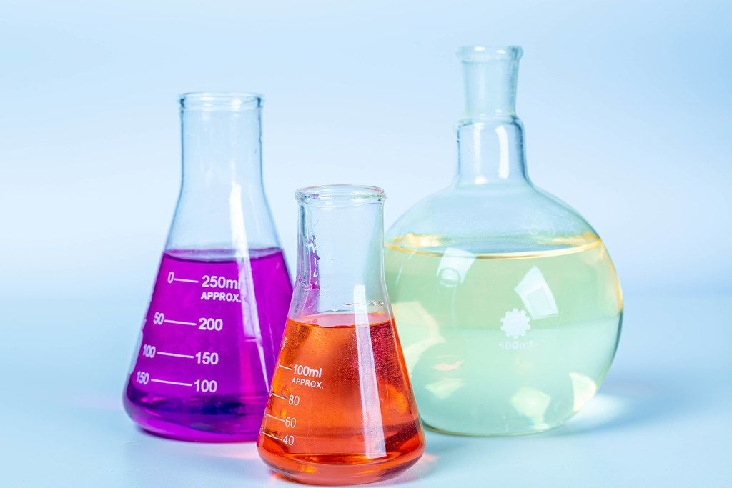 Laboratory glassware with colored liquids on light background