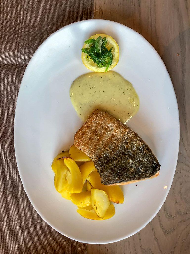Lachsfilet-Fisch vom Grill mit Kartoffeln und Kräuterdressing neben einer Zitrone auf einem weißen ovalen Teller