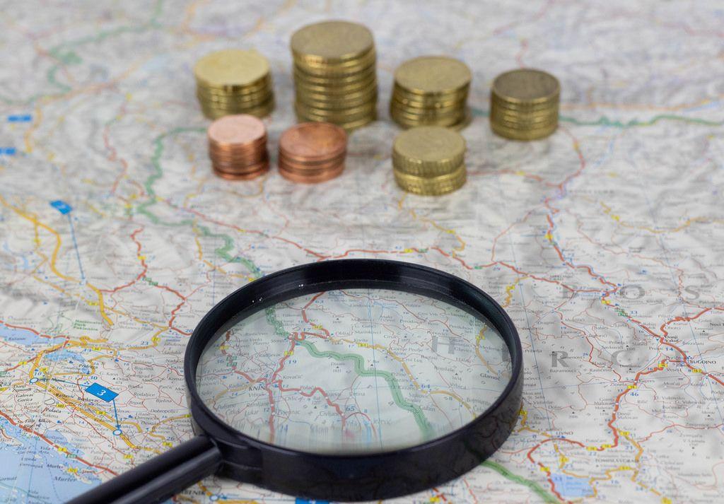 Landkarte für den Urlaub mit Lupe und Kleingeld