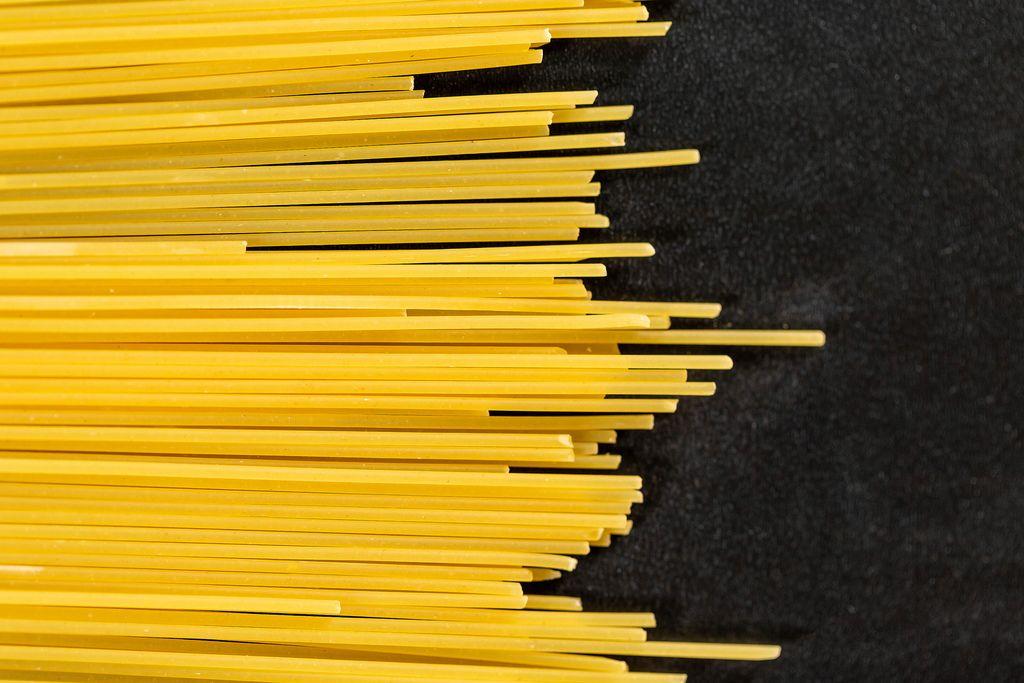 Lange gelbe Spaghetti vor dunklem Hintergrund
