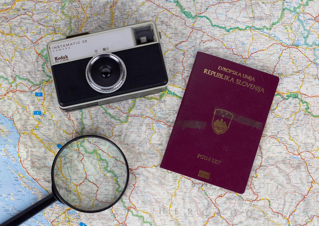 Langersehnte Reise nach Europa. Lupe, Kompaktkamera und Reisepass auf einer Landkarte