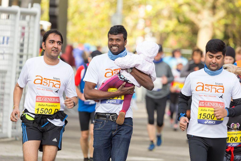 Läufer mit einem Baby in seinen Händen - Frankfurt Marathon 2017
