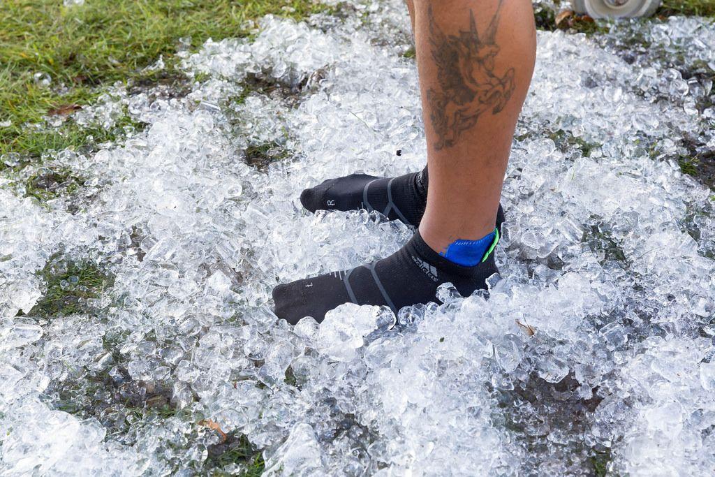 Läufer steht auf Eiswürfeln, um Füße zu kühlen