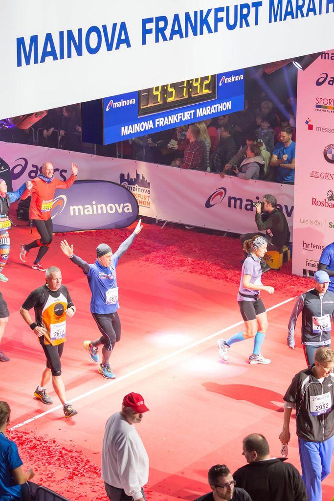 Läufer wirft seine Hände hoch beim überqueren der Ziellinie - Frankfurt Marathon 2017