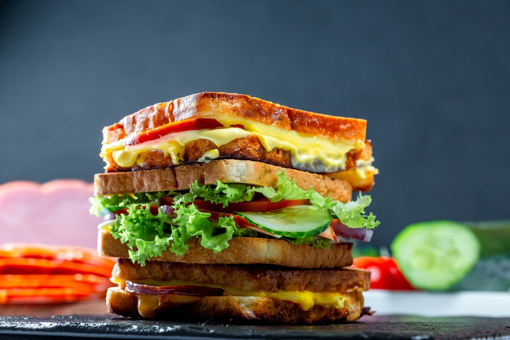 Layered sandwich with vegetables, ham and cheese