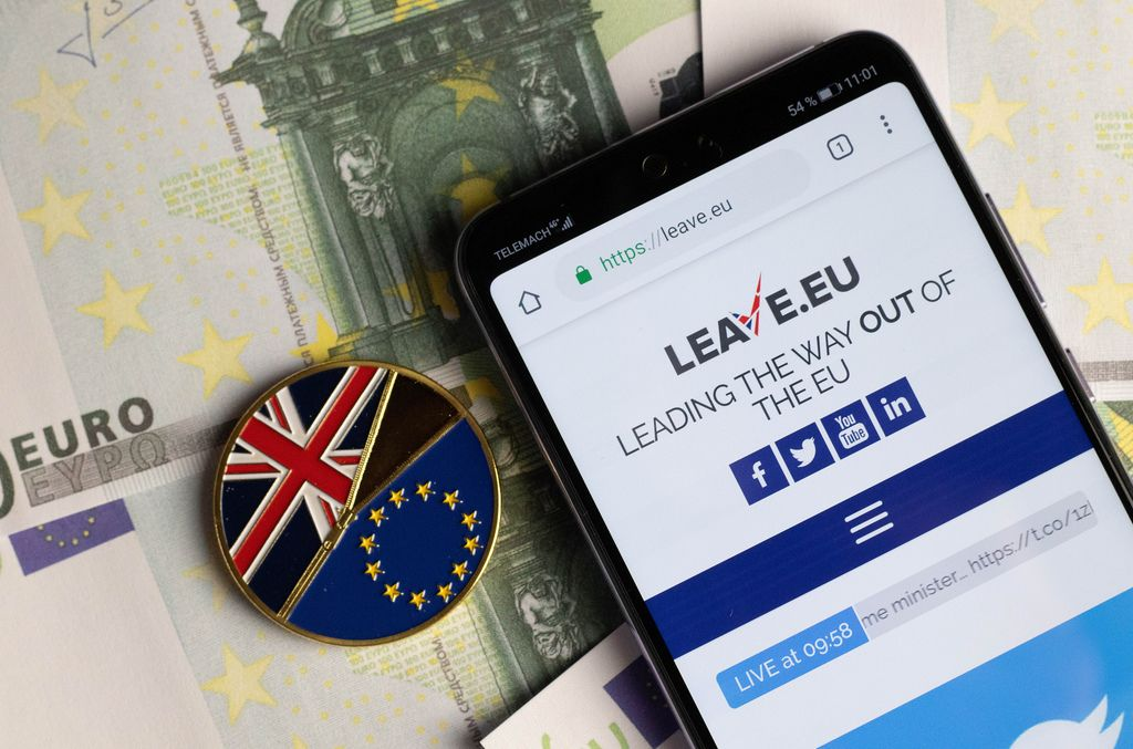Leave.eu website on mobile phone with Brexit medal coin on Euro banknotes