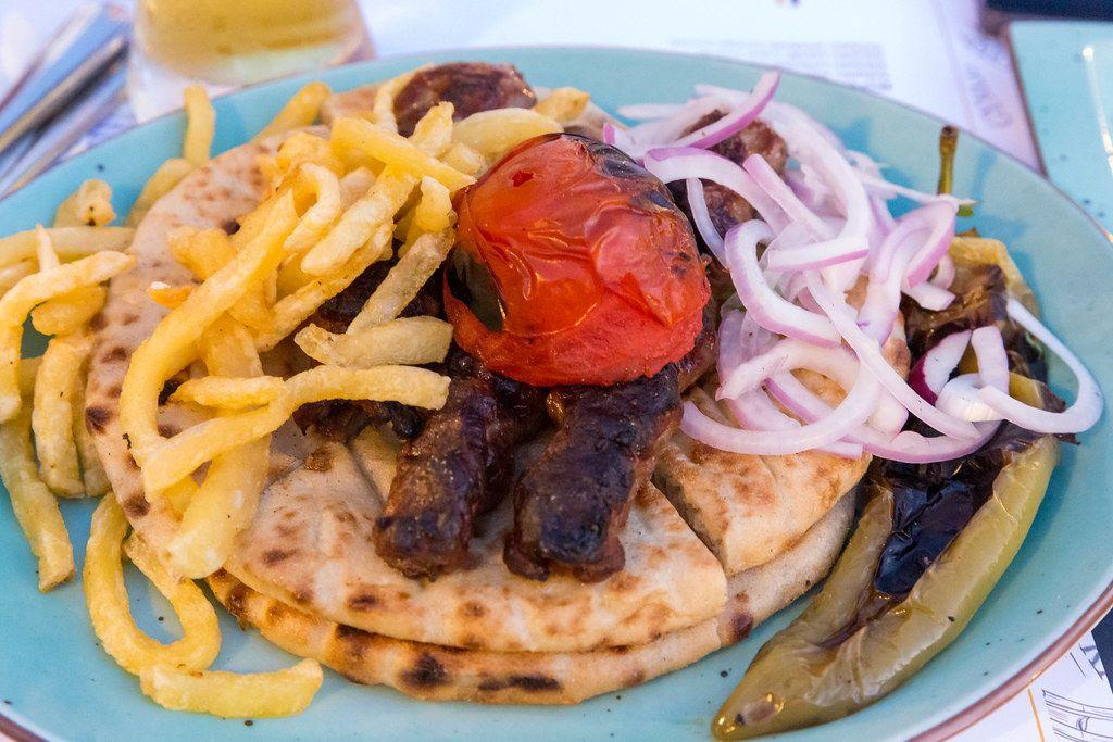 Leckere Kebab Pita mit Tomaten aus Paros, Zwiebeln und gegrillter griechischer Paprika auf blauem Teller