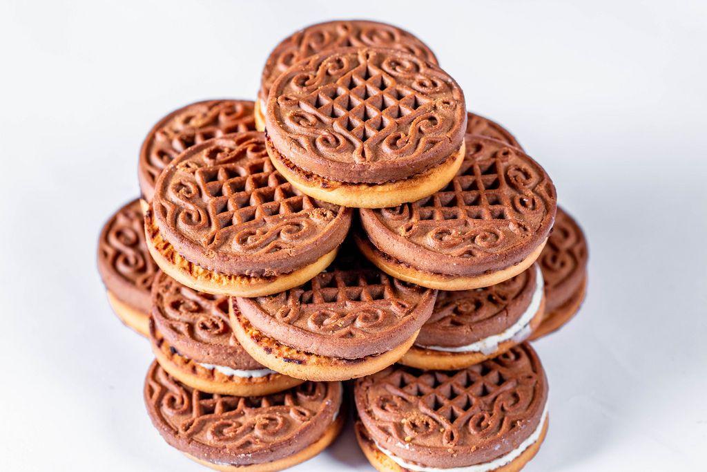 Leckere, runde Schokoladekekse mit Cremefüllung gestapelt vor weißem Hintergrund