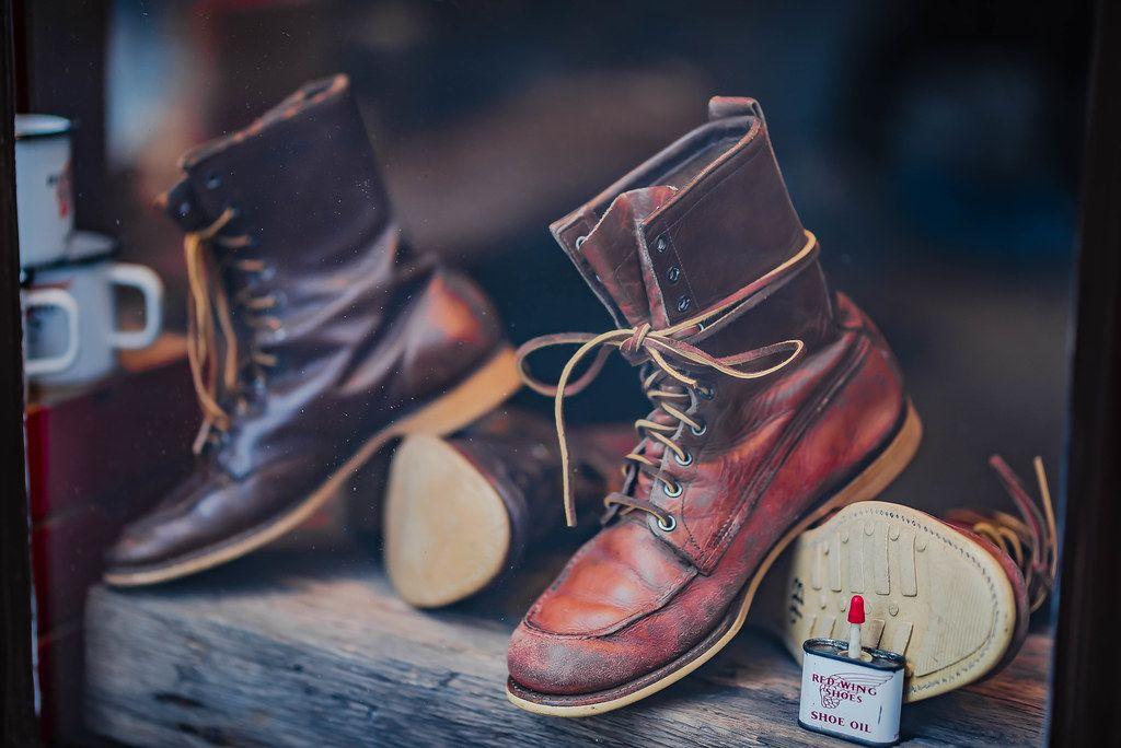 Lederstiefel auf einem Holzstamm ausgestellt im Schaufenster eines Schuhgeschäfts