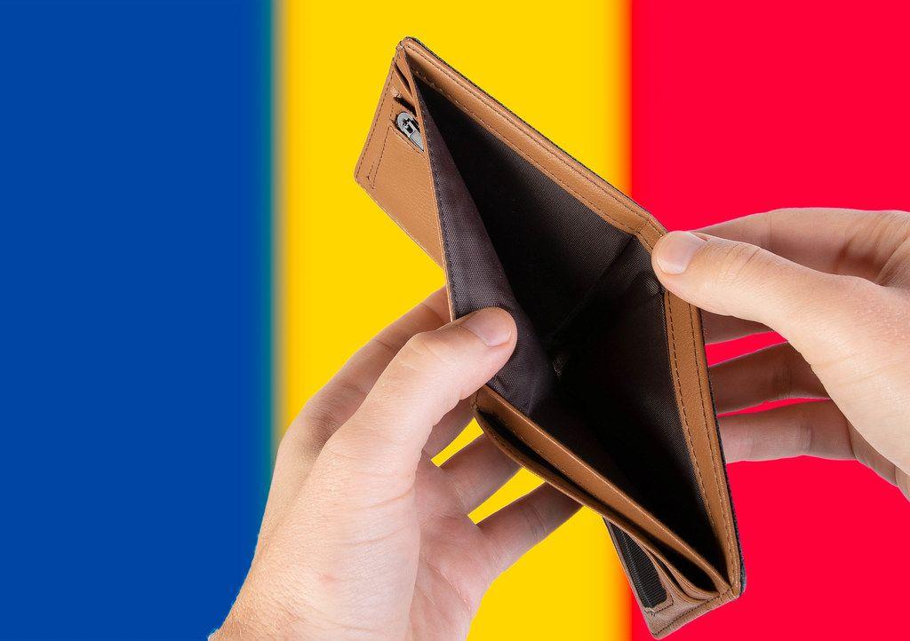 Leerer Geldbeutel aus Leder mit Flagge von Romänien. Rezession und Finanzkrise werden mit mehr Schulden und Bundeshaushaltdefizit einhergehen
