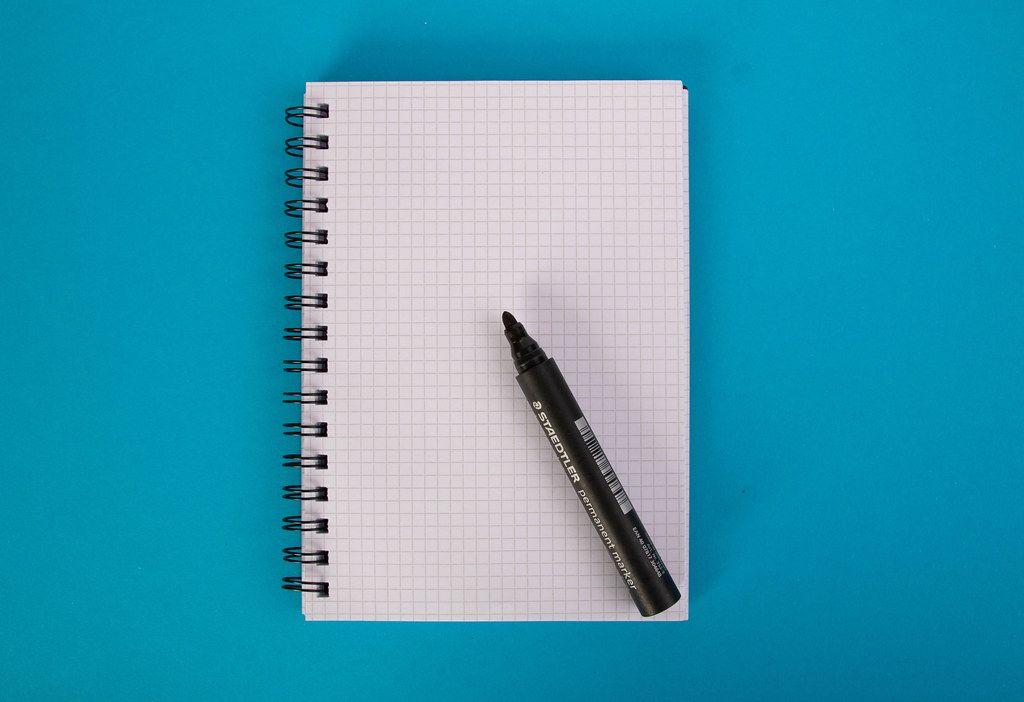 Leerer Notizblock mit schwarzem Textmarker, vor blauem Hintergrund