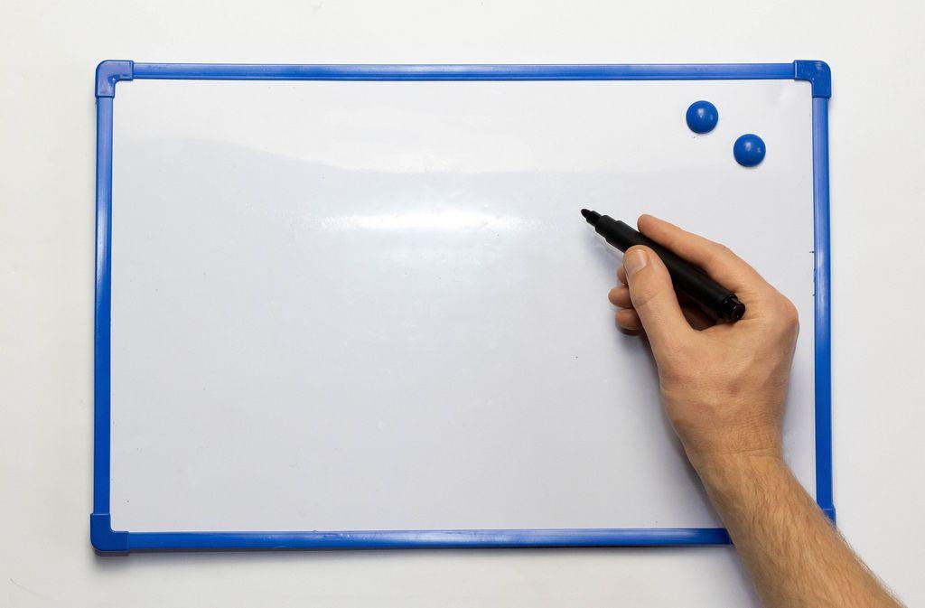 Leeres Whiteboard mit blauem Rahmen und blauen Magneten mit Hand und schwarzem Markierstift - Nahaufnahme frontal