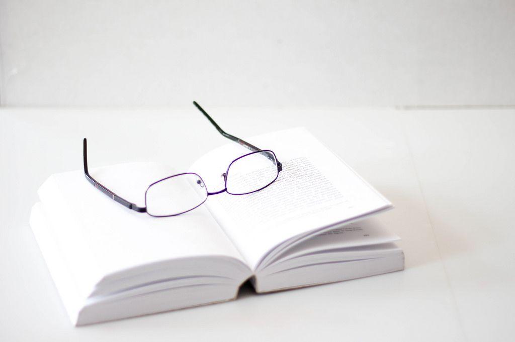 Lesebrille auf einem aufgeschlagenen Buch vor weißem Hintergrund