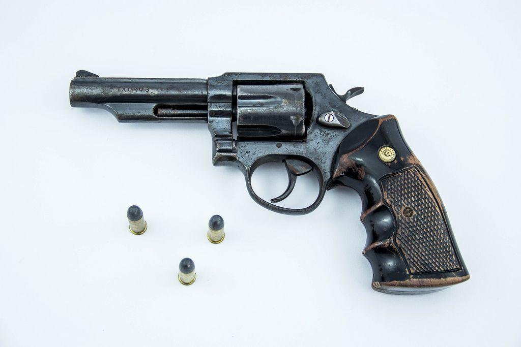 Liegender Revolver mit drei Patronen auf weißem Hintergrund