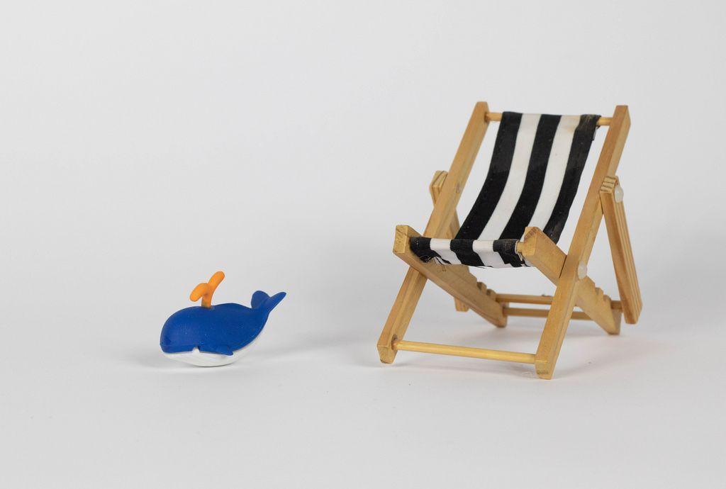 Liegestuhl und kleines Spielzeug in Form eines Wales