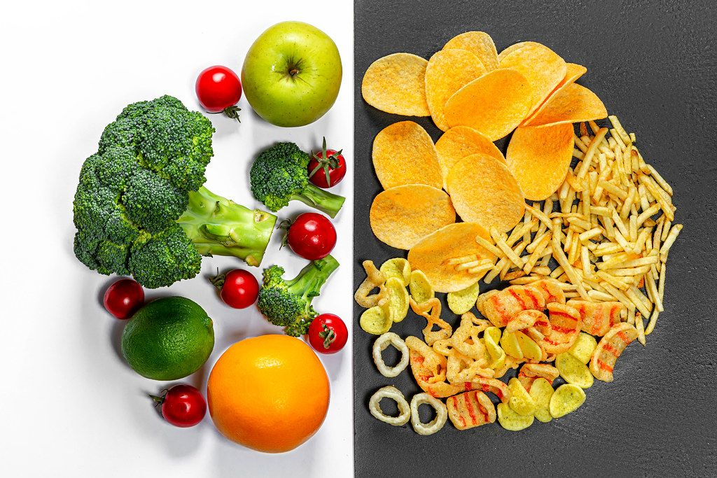 Lifestyle-choice-concept-Healthy-food-on-white-and-junk-food-on-a-black-background-Top-view.jpg