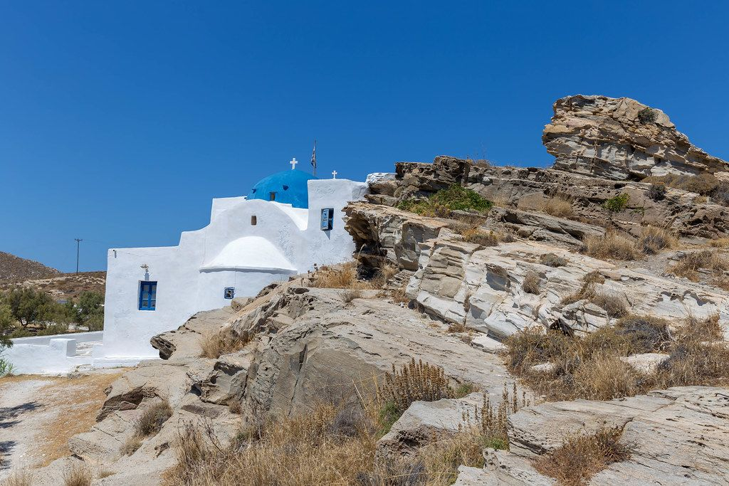 Limestone monastery St. John's of Deti, with blue dome, in the environmental park of Paros on Greece, built on a rocky coast at the Aegean Sea