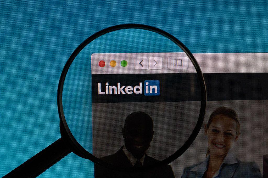 Linkedin Schriftzug und Logo, vergrößert dargestellt durch eine Lupe