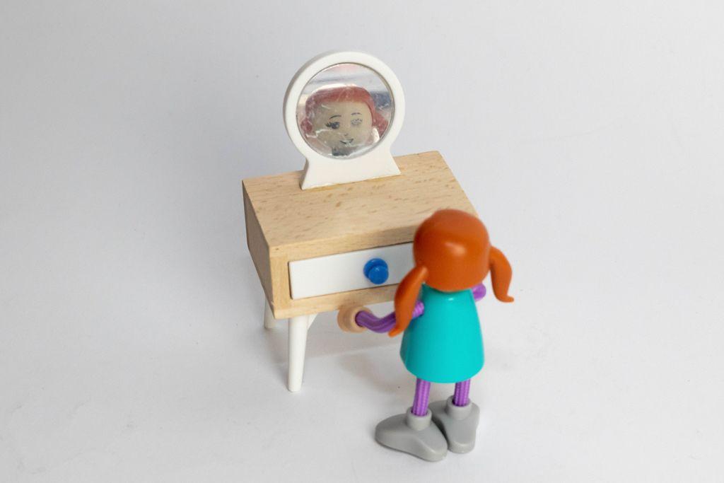 Little girl looks in the mirror