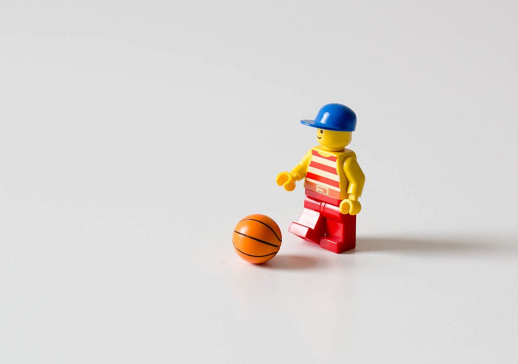 Little Lego with a hat and basketball on a white background