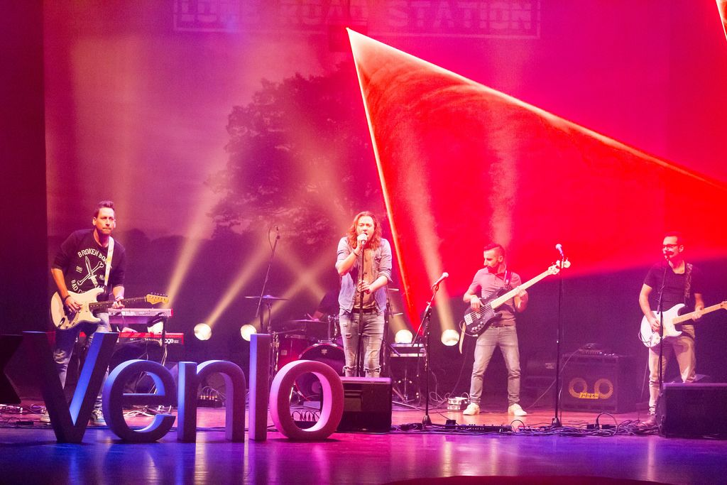Lone Road Station & Laserforum on the stage with Venlo sign in the foreground - TEDxVenlo 2017