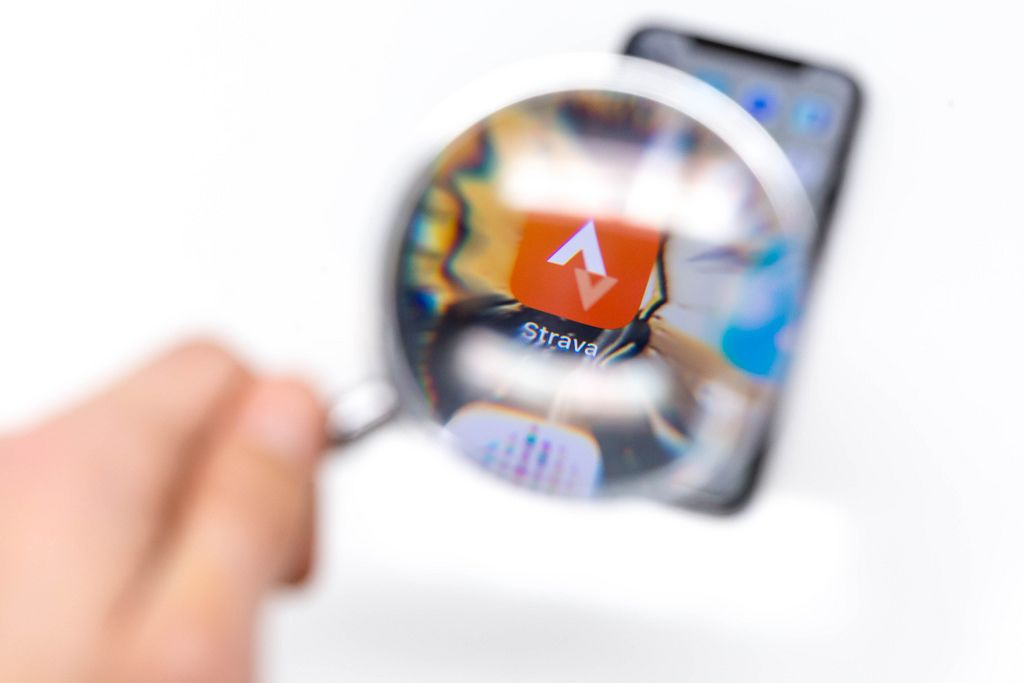 Looking through magnifying glass on Strava app on black cellphone in front of white background