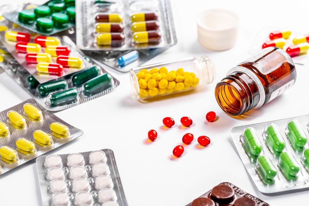 Lots of colorful and different shapes of pills, pills and capsules on white background (Flip 2019)