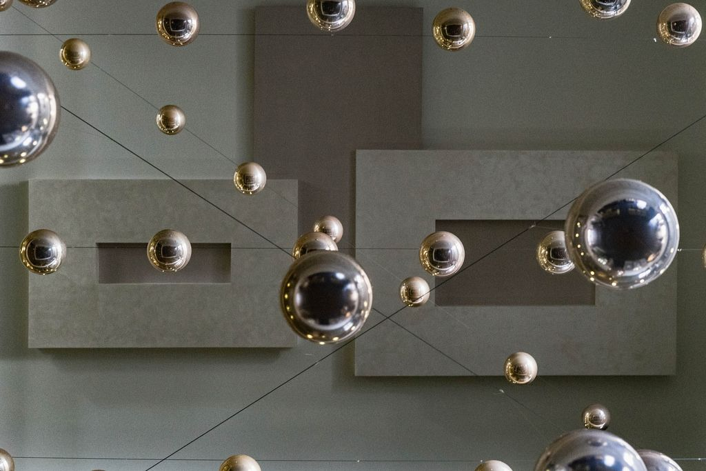 Low Angle Shot on Shiny Metal Balls Hanging From CEiling