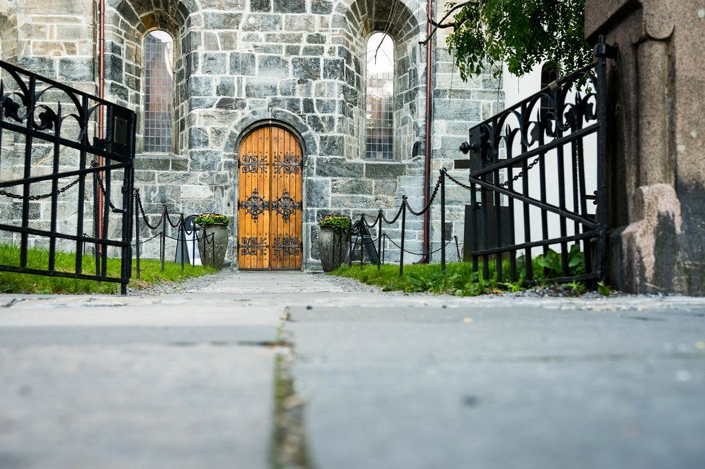 Low view of wooden church door with an open forged iron gate in foreground (Flip 2019)