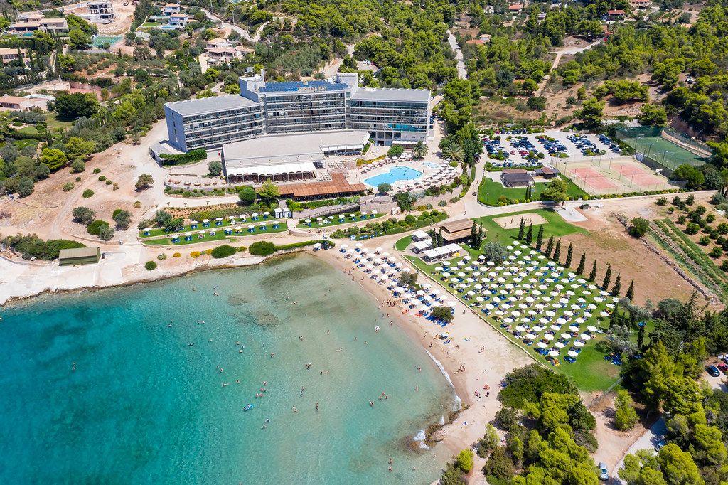 Luftaufnahme des modernen Strandhotels Aks Hinitsa Bay und Urlaubsgästen im grünen Meer vor Chinitsa, Griechenland