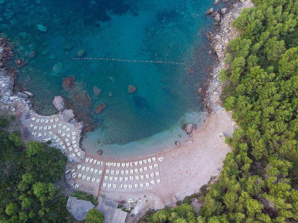 Luftaufnahme des Sutomore-Strands mit Liegestühlen, vor dem blauen Meer