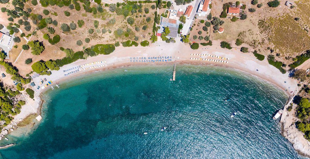 Luftaufnahme mit Sicht auf den Strand Paralia Agii Anargiri, in einer Bucht mit klarem grünem Wasser des Mystischen Meeres, in Griechenland