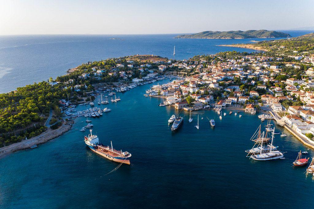 Luftaufnahme zeigt ein geankertes Frachtschiff und Segelboote im alten Hafen der Argosaronischen Insel Spetses, Griechenland, südlich von Piräus