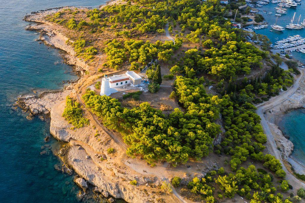 Luftaufnahme zeigt einen Leuchtturm auf dem abgelegen Teil der Insel Spetses, Griechenland, neben der Hafeneinfahrt