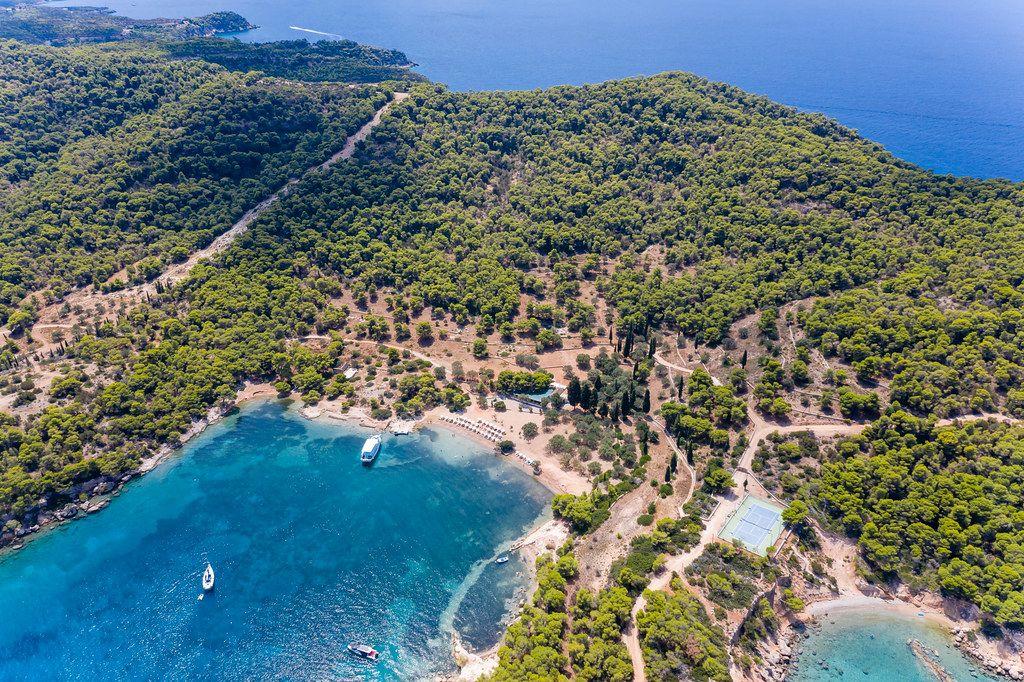 Luftbild der griechischen Insel Spetses mit seinem grünen Pinienwald und der Küste am Argolischen Golf