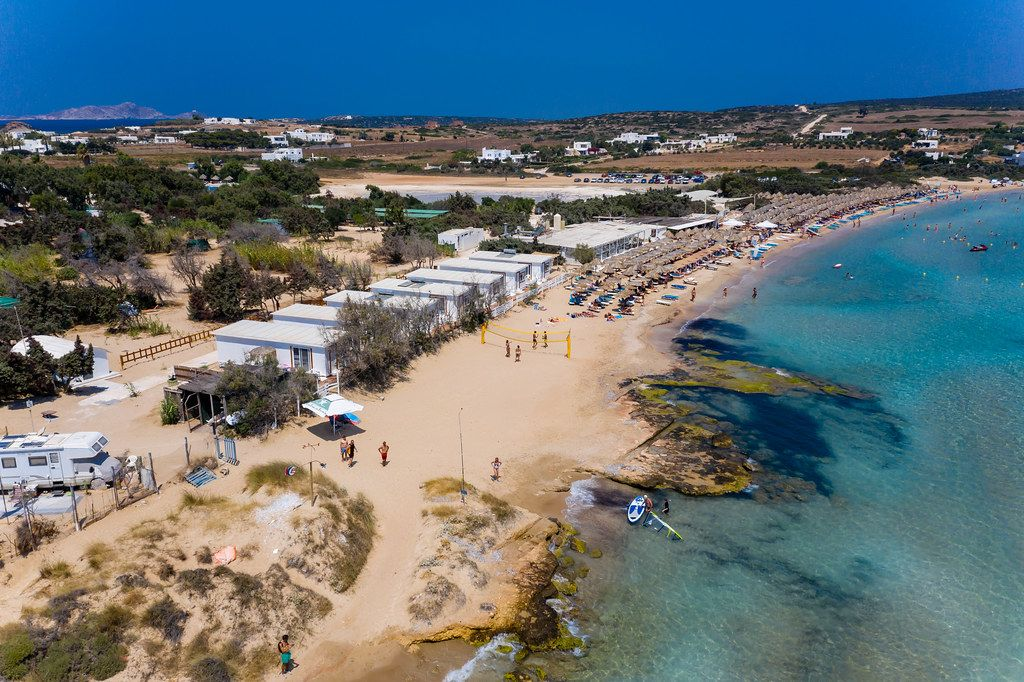 Luftbild des belebten Urlaubsorts und Strand Santa Maria auf Paros, Griechenland, mit Beachvolleyballfeld und Sonnenliegen