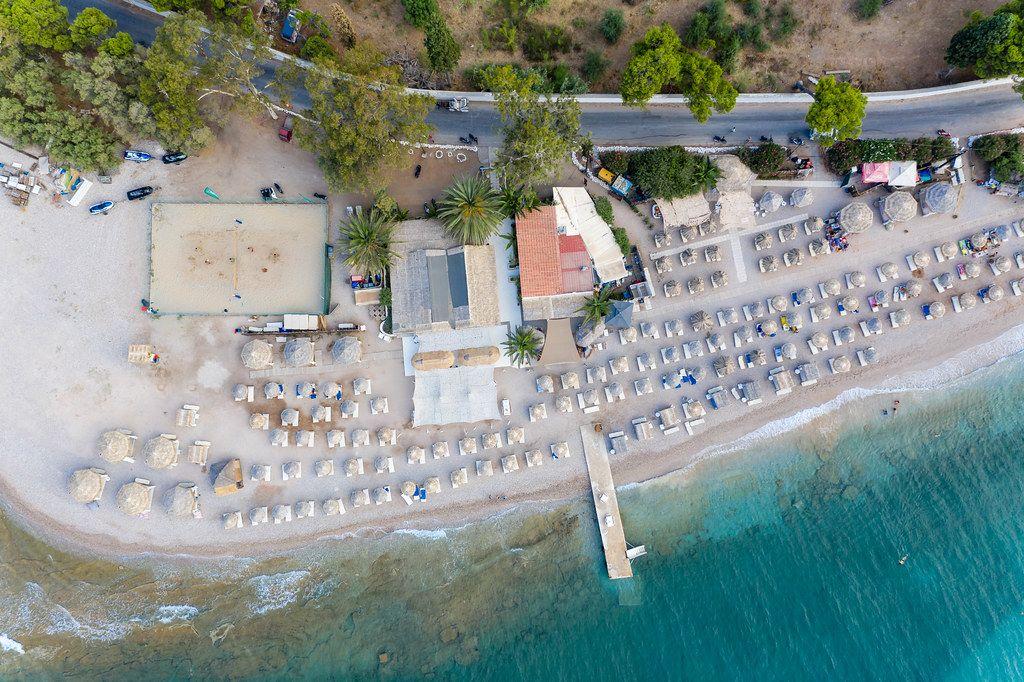 Luftbild des griechischen Καiκι-Strands, mit Bastsonnenschirmen und Touristen auf Strandliegen, an der Küste von Spetses