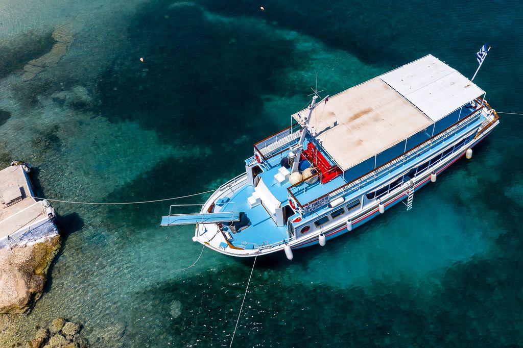 Luftbild einer blau-weißen Fähre mit Steg, im grünen Wasser des Argolischen Golfs, vor der Felsenküste von Spetses, Griechenland