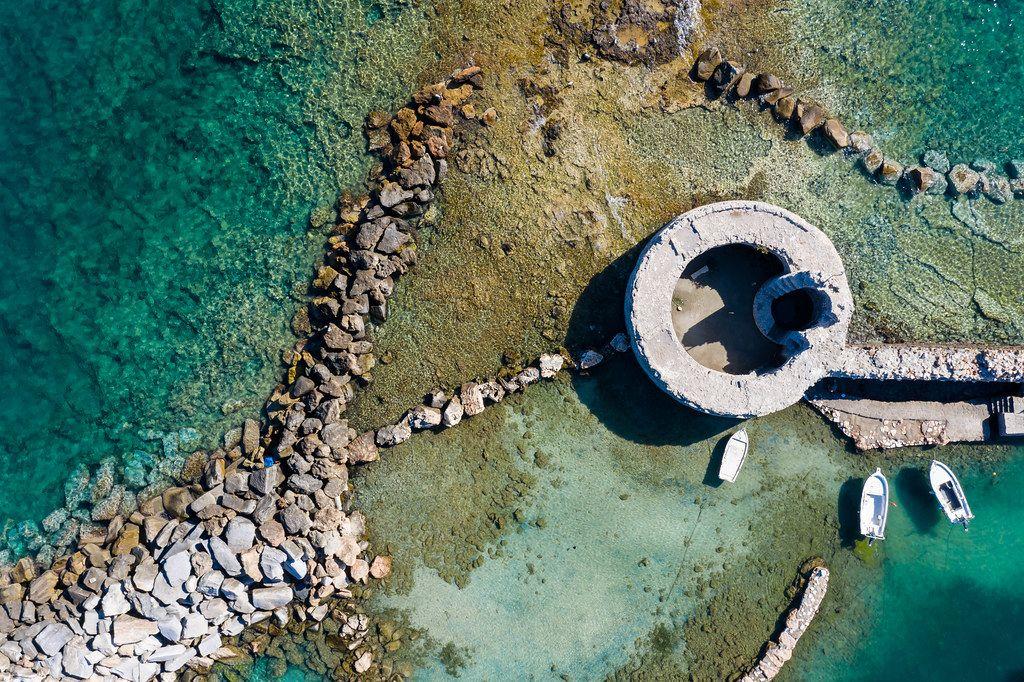 Luftbild einer venezianischen Burgruine mit Turm im Mittelmeer, vor der Hafenstadt Naoussa auf der griechischen Insel Paros