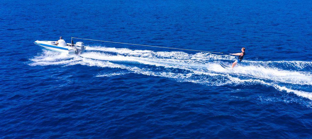 Luftbild eines stehenden Wasserskifahrers hinter einem Sportboot auf dem Agogischen Golf