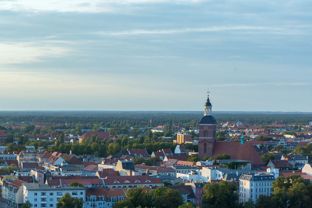Luftbild über Berliner Wohnhäuser und Kirche, mit blauem Himmel