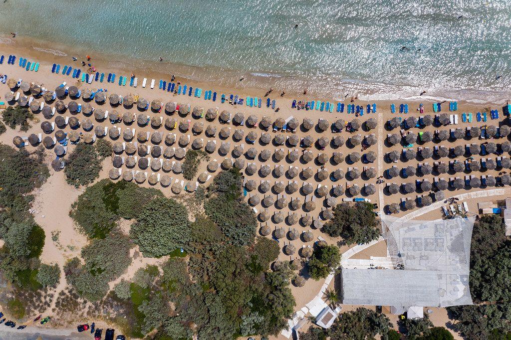 Luftbild von aufgereihten Bast-Sonnenschirmen auf dem weißen Sandstrand Santa Maria auf Paros, Griechenland, am türkisfarbenen Mittelmeer