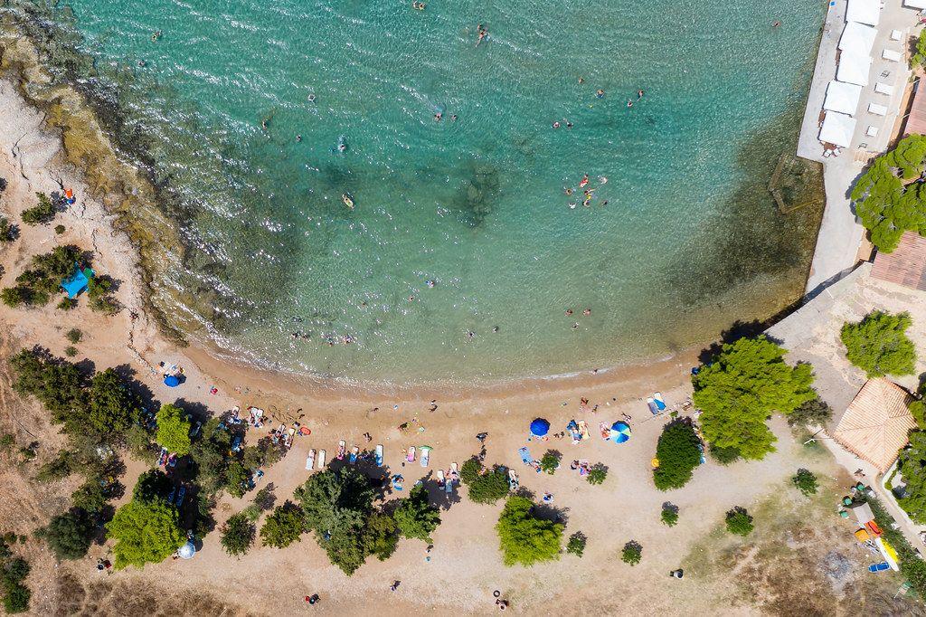 Luftbild von Touristen am Sandstrand Hinitsa in der Urlaubsregion Porto Heli, Griechenland, am Argolischen Golf