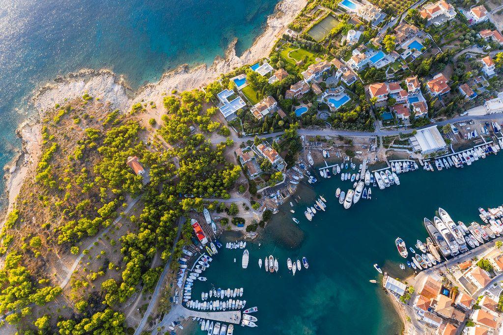 Luftbild von Wohnhäusern und Hotels mit Pool an der Hafenbucht von Kouzounos, südöstlich von Spetses, Griechenland